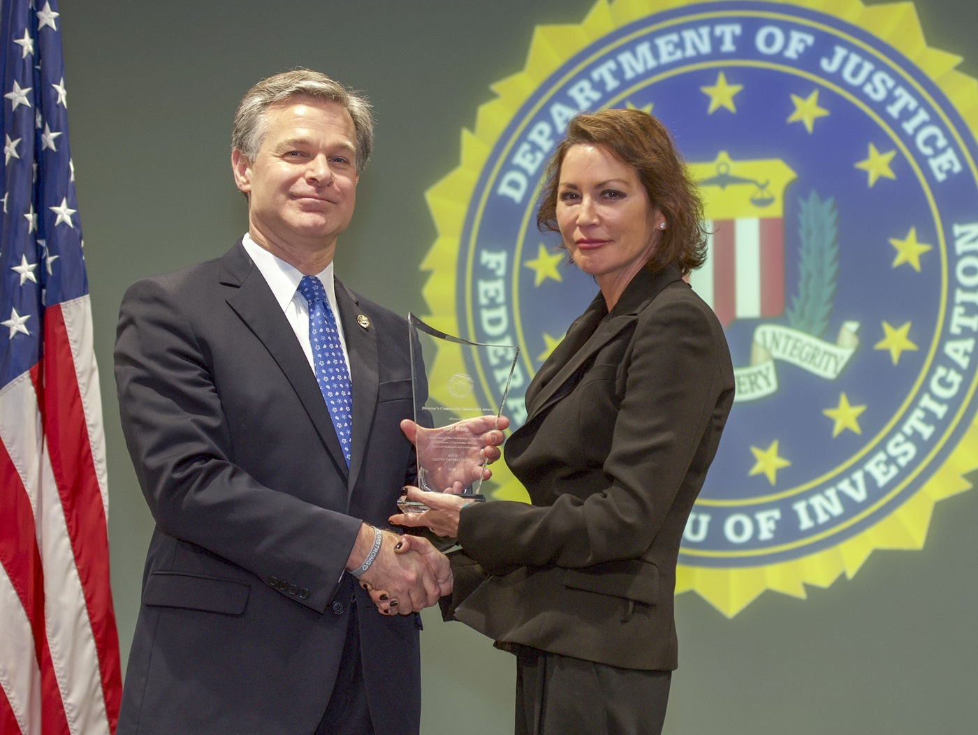 FBI Director Christopher Wray presents Los Angeles Division recipient Jodi Wing with the Director's Community Leadership Award (DCLA) at a ceremony at FBI Headquarters on May 3, 2019.