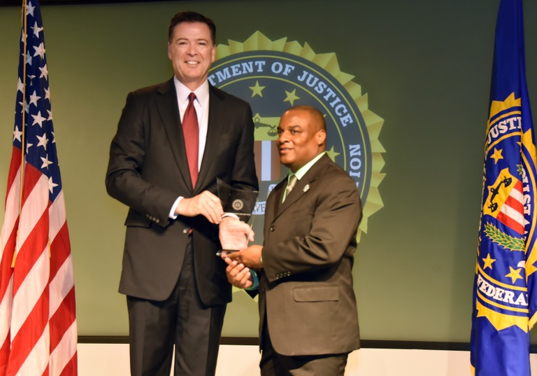 FBI Director James Comey presents Louisville Division recipient Jerome S. Bowles with the Director's Community Leadership Award (DCLA) at a ceremony at FBI Headquarters on April 28, 2017.