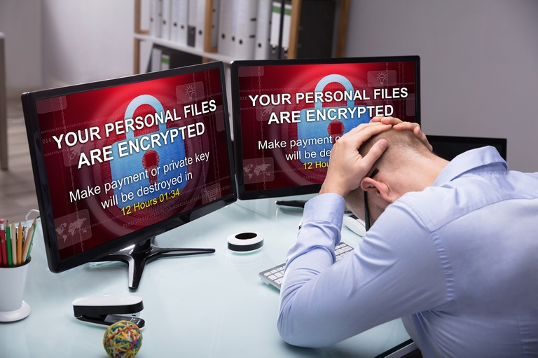 Stock image depicting distressed man in front of computer monitors displaying ransomware lock screens.