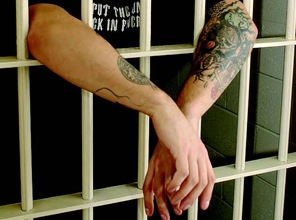 Man with arms protruding from prison cell. (From CJIS Link article)