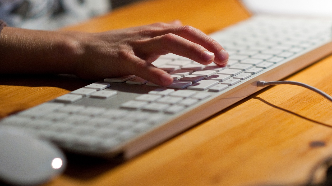 Stock image of a man's hand typing on a computer keyboard.