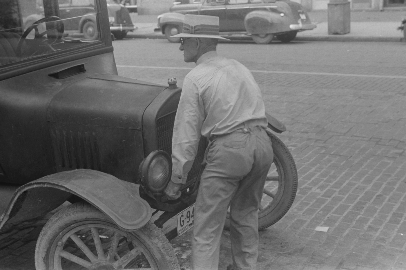 Black and white photo of man working on a 1938 Ford Model T car (Library of Congress photo)