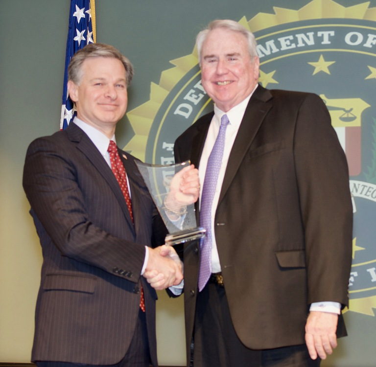FBI Director Christopher Wray presents Memphis Division recipient Henry L. Brenner with the Director's Community Leadership Award (DCLA) at a ceremony at FBI Headquarters on April 20, 2018.
