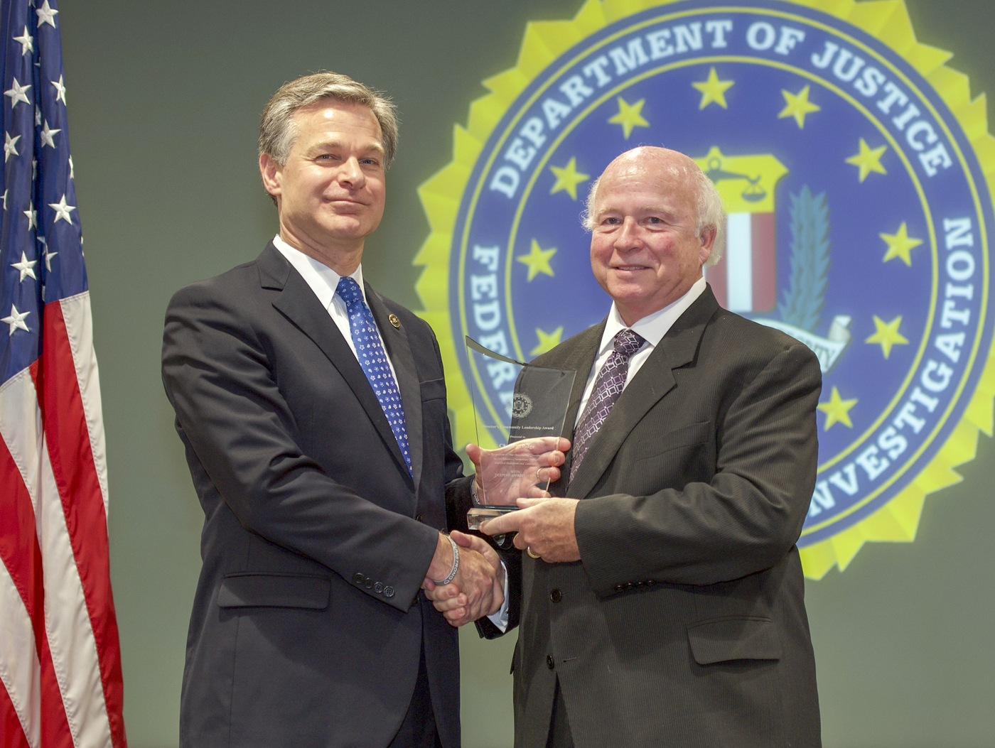 FBI Director Christopher Wray presents Miami Division recipient Charles Dodge with the Director's Community Leadership Award (DCLA) at a ceremony at FBI Headquarters on May 3, 2019.