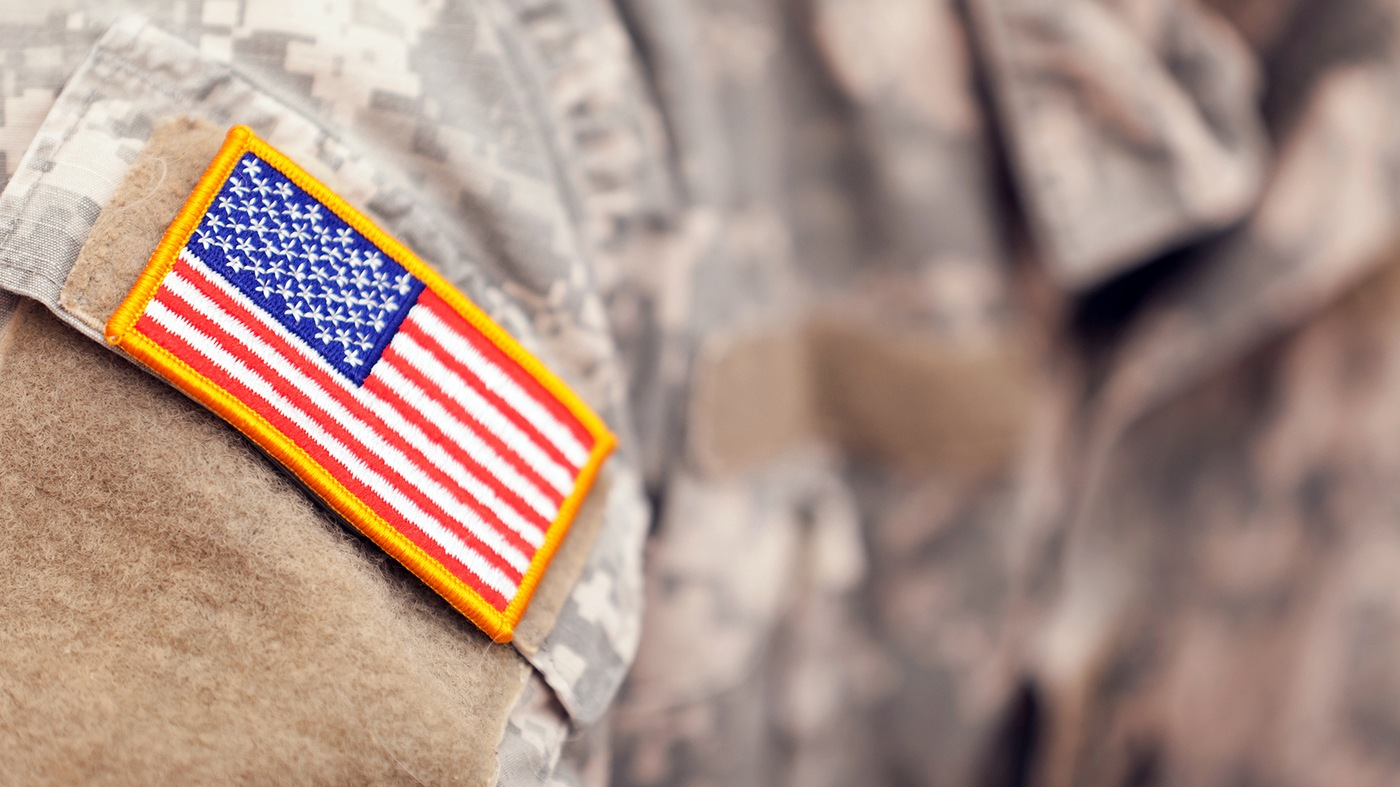Stock photo depicting an American flag patch on the sleeve of a camouflage military uniform.