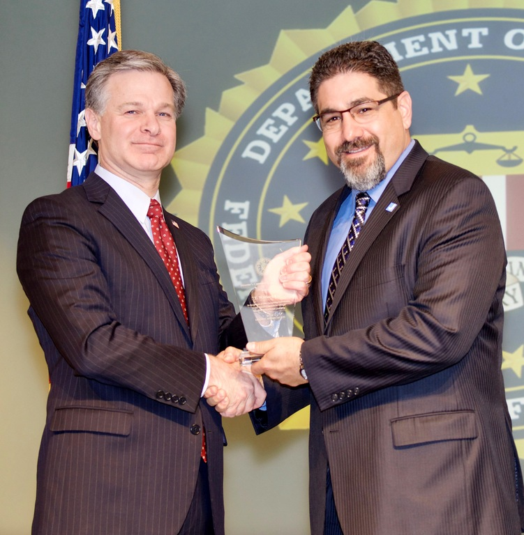 FBI Director Christopher Wray presents Milwaukee Division recipient Mark Shapiro with the Director's Community Leadership Award (DCLA) at a ceremony at FBI Headquarters on April 20, 2018.