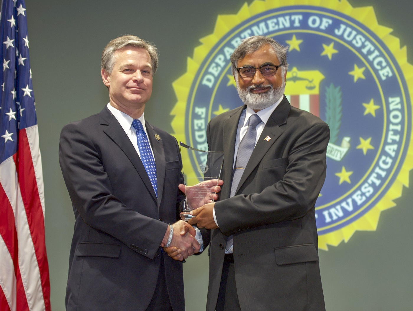FBI Director Christopher Wray presents Milwaukee Division recipient Masood Akhtar with the Director's Community Leadership Award (DCLA) at a ceremony at FBI Headquarters on May 3, 2019.