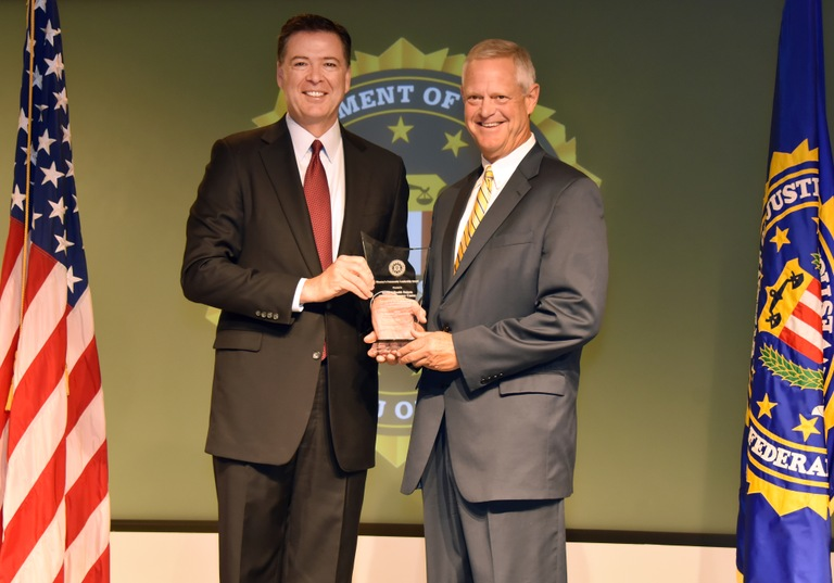 FBI Director James Comey presents Minneapolis Division recipient the Sanford Health Dakota Children's Advocacy Center (represented by Kelby Krabbenhoft) with the Director's Community Leadership Award (DCLA) at a ceremony at FBI Headquarters on April 28, 2017.