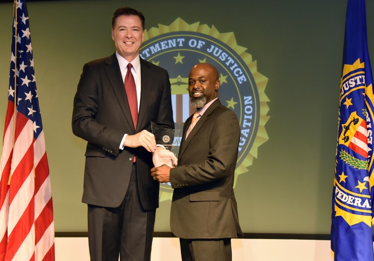 FBI Director James Comey presents Mobile Division recipient Kevin King with the Director's Community Leadership Award (DCLA) at a ceremony at FBI Headquarters on April 28, 2017.