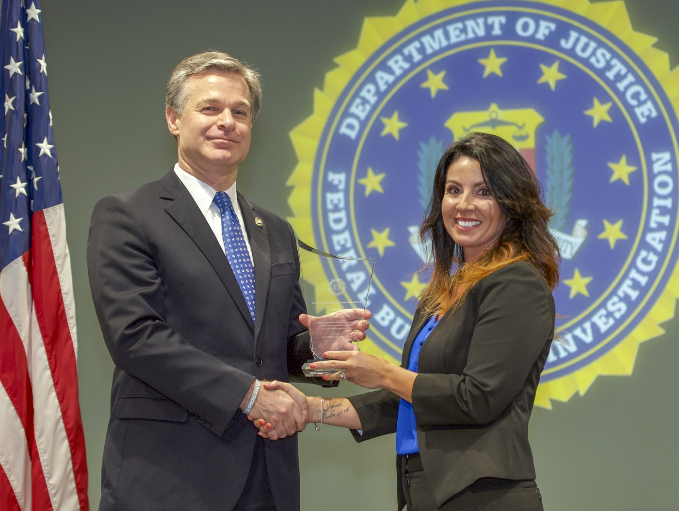 FBI Director Christopher Wray presents Mobile Division recipient The Rose Center (represented by Crystal Yarbrough) with the Director's Community Leadership Award (DCLA) at a ceremony at FBI Headquarters on May 3, 2019.