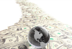 Stock image of a glass globe atop a trail of money.