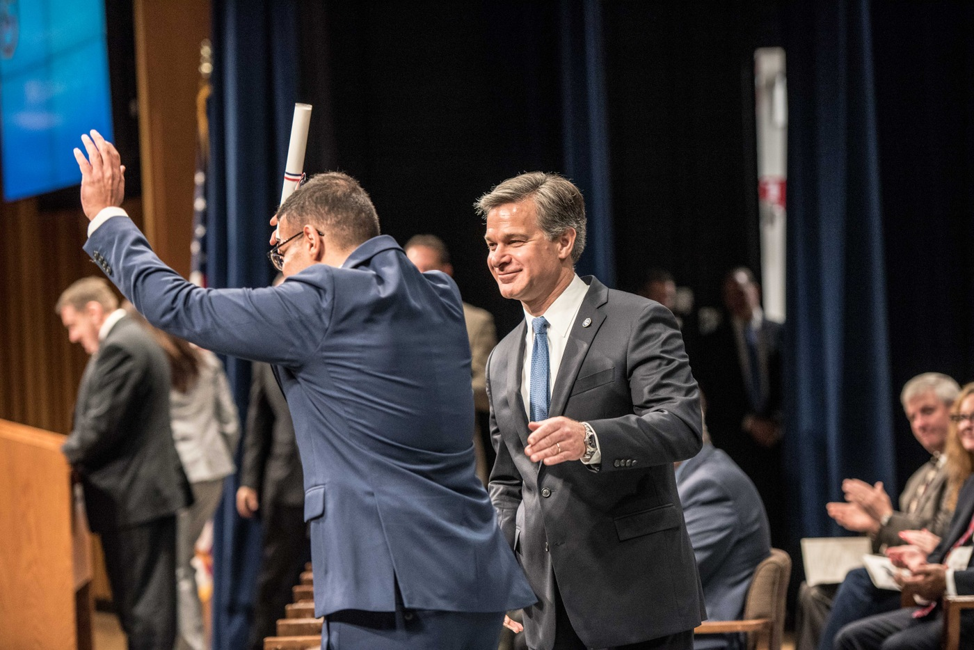 A National Academy graduate celebrates with FBI Director Christopher Wray during ceremony June 7, 2019.