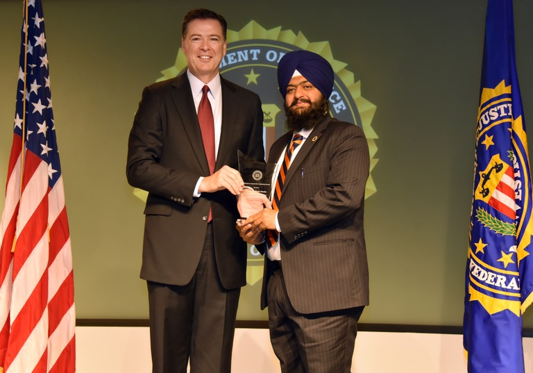 FBI Director James Comey presents New Haven Division recipient Swaranjit Singh Khalsa with the Director's Community Leadership Award (DCLA) at a ceremony at FBI Headquarters on April 28, 2017.