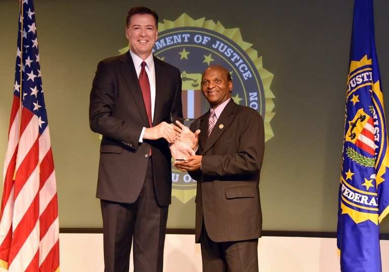 FBI Director James Comey presents New Orleans Division recipient Dr. Earnest L. Johnson with the Director's Community Leadership Award (DCLA) at a ceremony at FBI Headquarters on April 28, 2017.