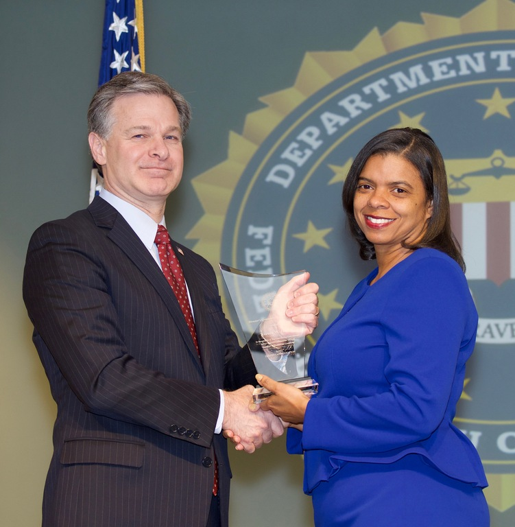 FBI Director Christopher Wray presents New Orleans Division recipient Noreen Jacobs with the Director's Community Leadership Award (DCLA) at a ceremony at FBI Headquarters on April 20, 2018.
