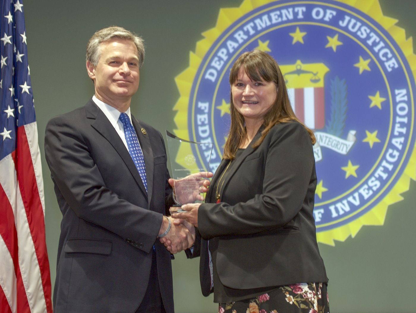 FBI Director Christopher Wray presents New Orleans Division recipient the Baptist Friendship House (represented by Kay Bennett) with the Director's Community Leadership Award (DCLA) at a ceremony at FBI Headquarters on May 3, 2019.