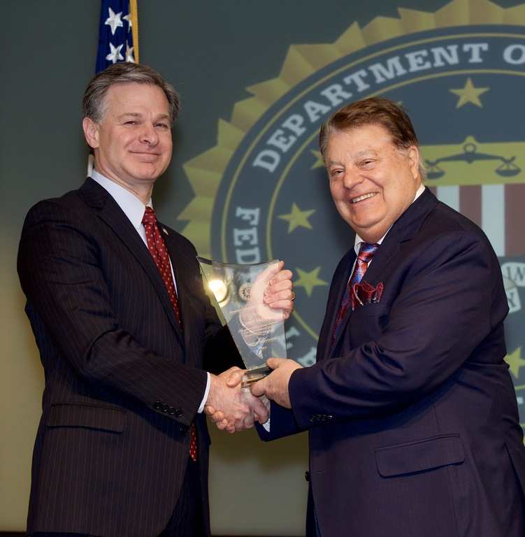 FBI Director Christopher Wray presents New York Division recipient the Council for Unity (represented by Robert J. De Sena) with the Director's Community Leadership Award (DCLA) at a ceremony at FBI Headquarters on April 20, 2018.
