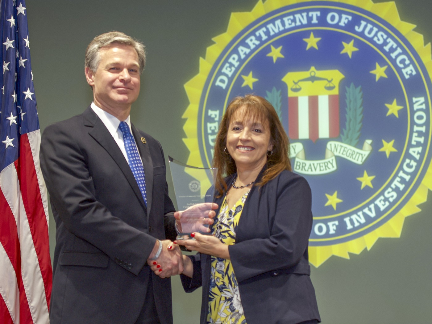 FBI Director Christopher Wray presents New York Division recipient the Suffolk County Child Advocacy Center (represented by Andrea Ramos-Topper) with the Director's Community Leadership Award (DCLA) at a ceremony at FBI Headquarters on May 3, 2019.