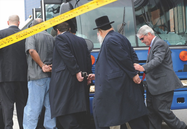 FBI agents in Newark lead arrested suspects in a political corruption and money laundering probe onto a bus in July 2009. AP Photo.