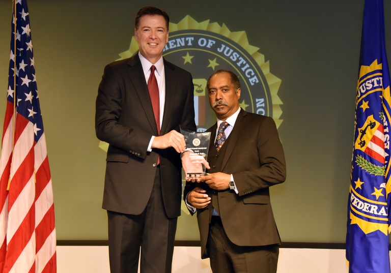 FBI Director James Comey presents Newark Division recipient Pastor John R. Taylor with the Director's Community Leadership Award (DCLA) at a ceremony at FBI Headquarters on April 28, 2017.