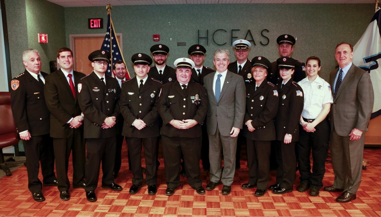 On April 14, 2015, Huntington County Executive Steve Bellone and Suffolk County Fire, Rescue, and Emergency Services Commissioner Joe Williams honored members of the Huntington Community First Aid Squad who recently responded to a call to aid an injured police officer. Among those recognized at the ceremony was FBI Supervisory Special Agent (SSA) Michael Petronella, who dedicates his time to riding with the local squad on Wednesday nights as an EMT.