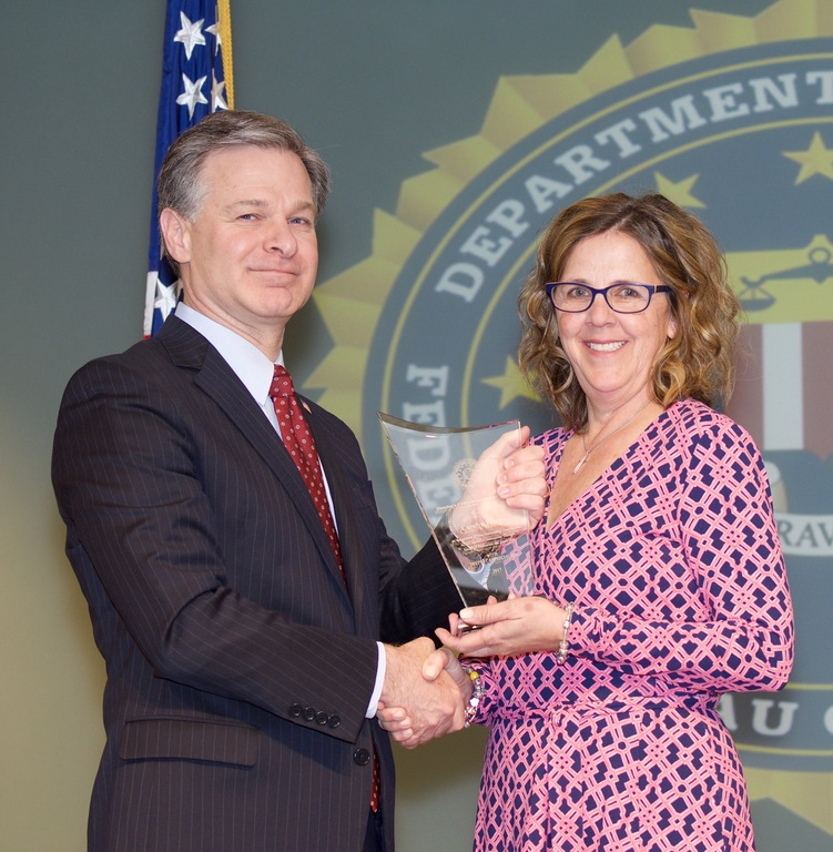 FBI Director Christopher Wray presents Norfolk Division recipient Carolyn Weems with the Director's Community Leadership Award (DCLA) at a ceremony at FBI Headquarters on April 20, 2018.