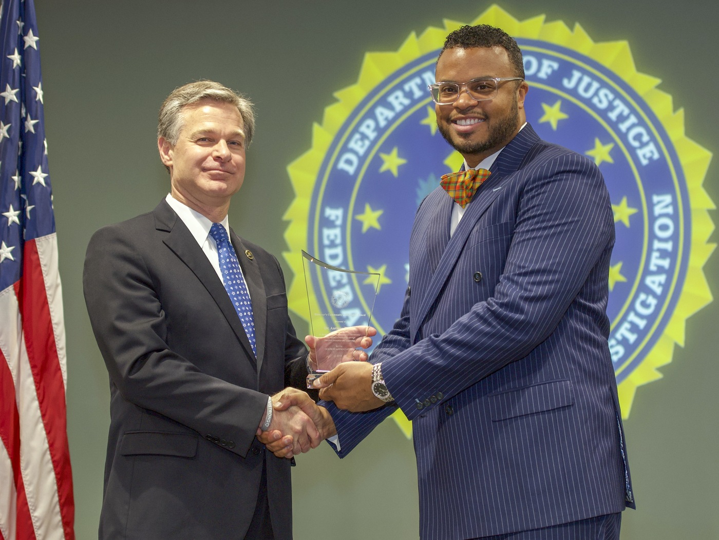 FBI Director Christopher Wray presents Norfolk Division recipient Dr. Antipas Harris with the Director's Community Leadership Award (DCLA) at a ceremony at FBI Headquarters on May 3, 2019.