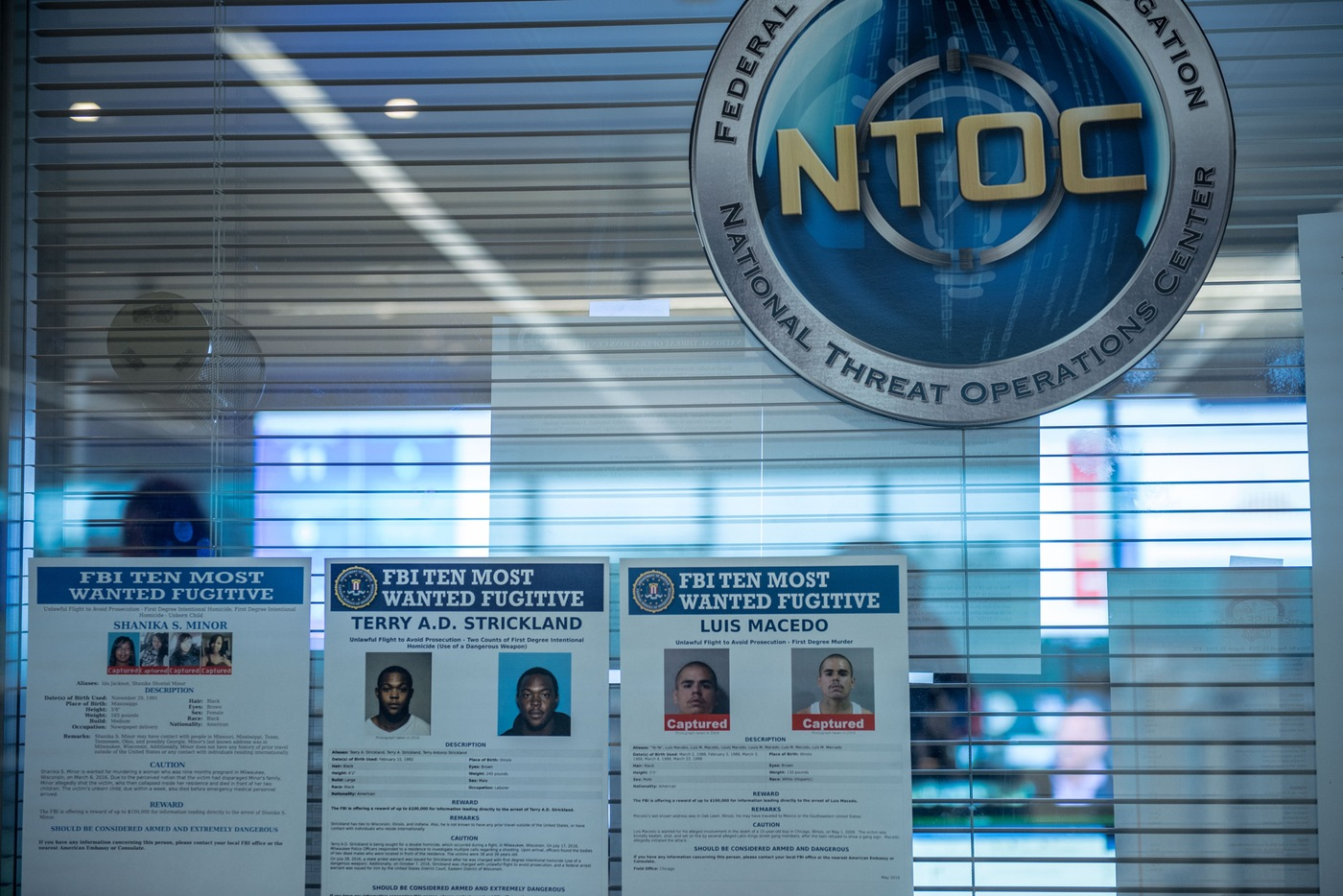 Posters of three of the FBI's Ten Most Wanted Fugitives in a window under the National Threat Operations Center seal.