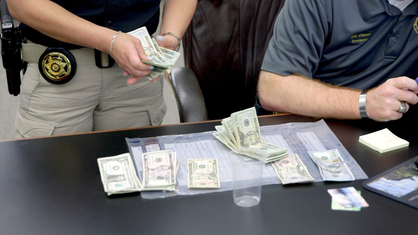 Houston Police officers count money they found on a suspected pimp who was apprehended during Operation Independence Day, a monthlong nationwide operation to find human traffickers and rescue underage trafficking victims.