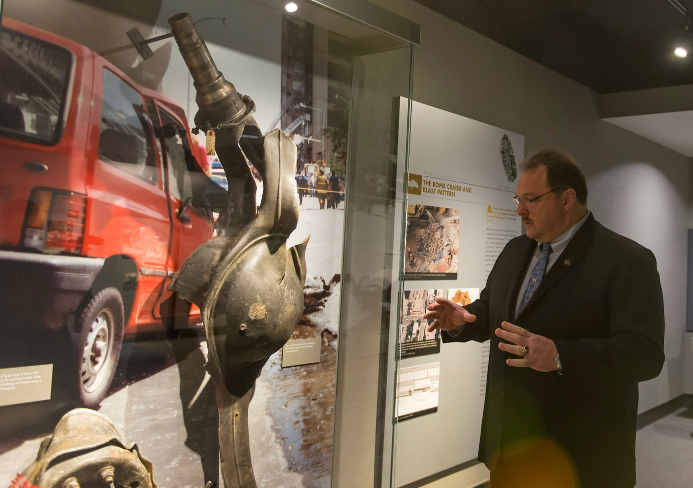 FBI Oklahoma City Special Agent Barry Black shows the damaged rear axle of a Ryder rental truck that is on display at the Oklahoma City National Memorial and Museum. The serial number on the axle helped lead investigators to the bomber, Timothy McVeigh.