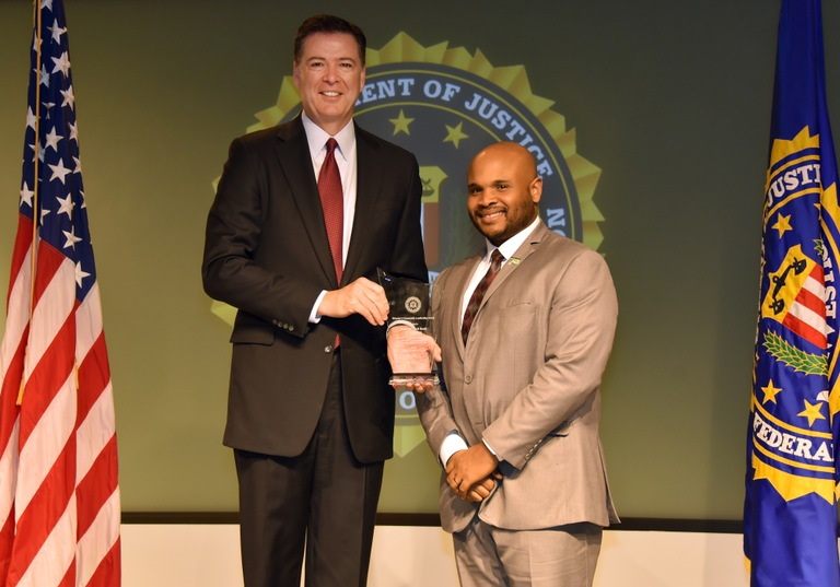 FBI Director James Comey presents Oklahoma City Division recipient the Regional Food Bank of Oklahoma (represented by Stephen Bobb-Semple, II) with the Director's Community Leadership Award (DCLA) at a ceremony at FBI Headquarters on April 28, 2017.
