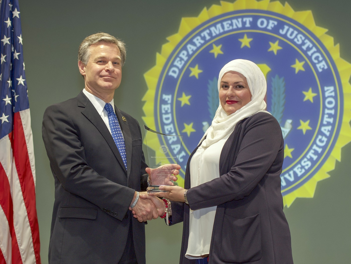 FBI Director Christopher Wray presents Oklahoma City Division recipient Aliye Shimi with the Director's Community Leadership Award (DCLA) at a ceremony at FBI Headquarters on May 3, 2019.