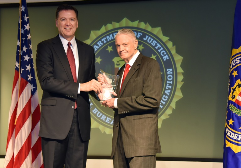 FBI Director James Comey presents Omaha Division recipient Dr. Tom Osborne with the Director's Community Leadership Award (DCLA) at a ceremony at FBI Headquarters on April 28, 2017.