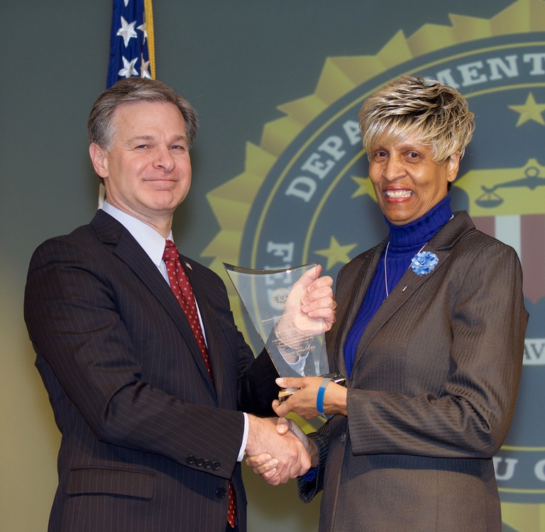 FBI Director Christopher Wray presents Omaha Division recipient Dr. Sandra McGee with the Director's Community Leadership Award (DCLA) at a ceremony at FBI Headquarters on April 20, 2018.