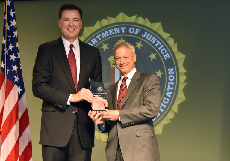 FBI Director James Comey presents Office of Public Affairs recipient The Gary Sinise Foundation (represented by Gary Sinise) with the Director's Community Leadership Award (DCLA) at a ceremony at FBI Headquarters on April 28, 2017.