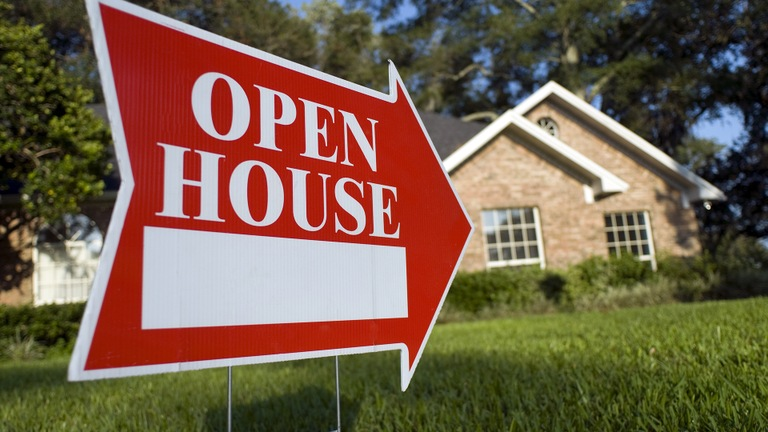 Stock image depicting an open house sign in front of a home.