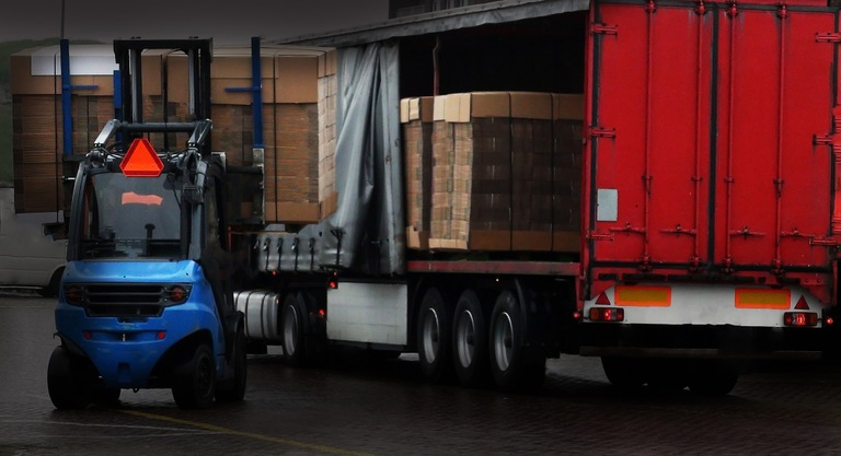 Stock image depicting pallets being loaded onto a tractor-trailer in a warehouse.