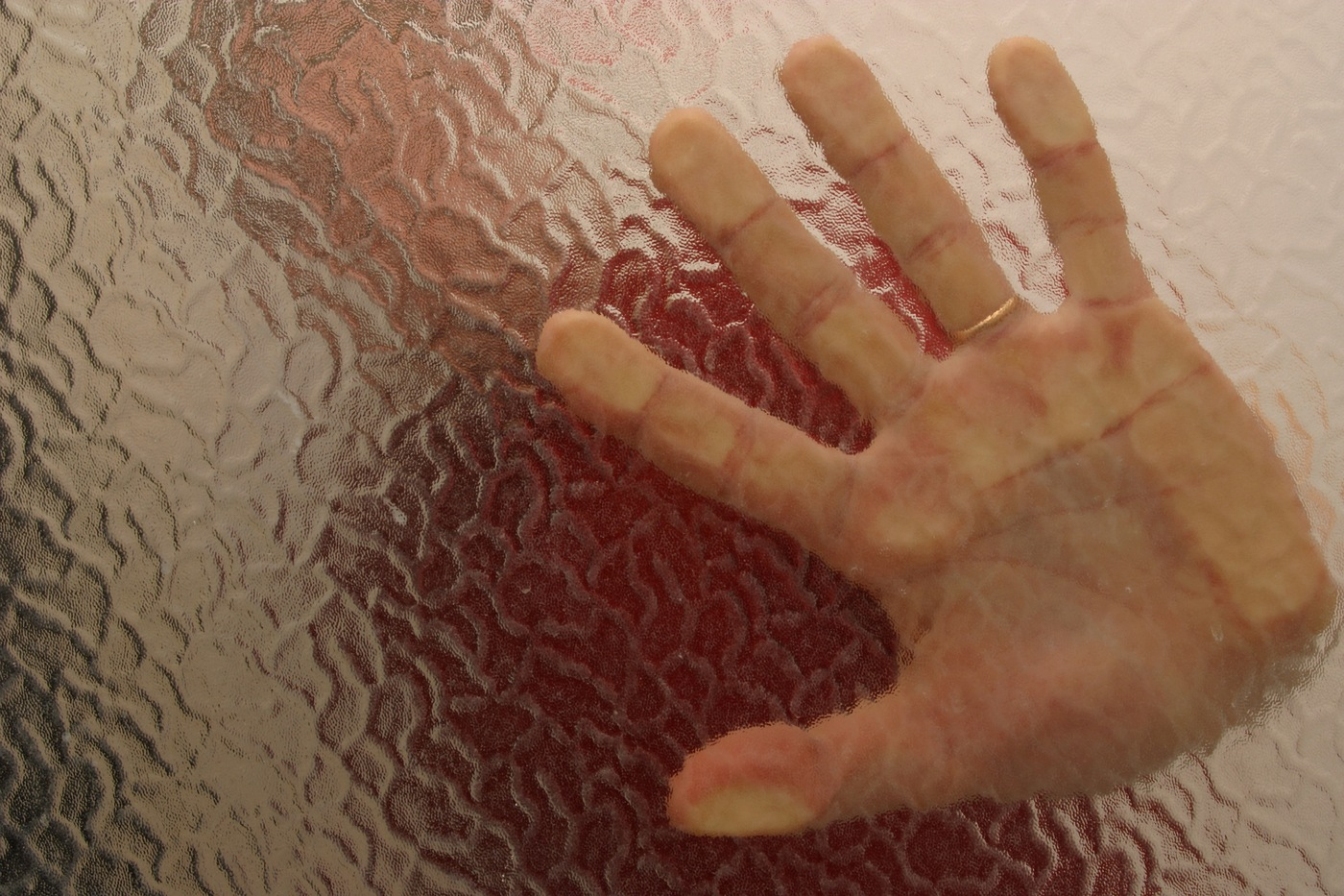 Stock image depicting person pressing palm against frosted glass. (From CJIS Link article)