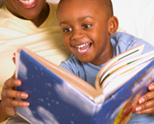 Adult in yellow collarless shirt reading with child in blue shirt on lap, blue colored book in front of both.