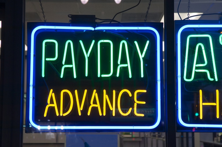 Stock image of a neon sign with the words Payday Advance.