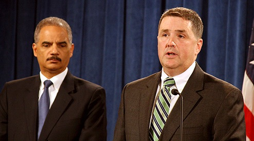 FBI Associate Deputy Director Kevin Perkins, right, is joined by Attorney General Eric Holder at a press conference announcing the results of the yearlong Distressed Homeowner Initiative in October 2012.