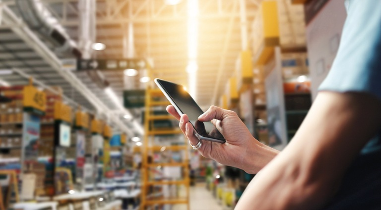 Stock image depicting a man using a cell phone in a warehouse.