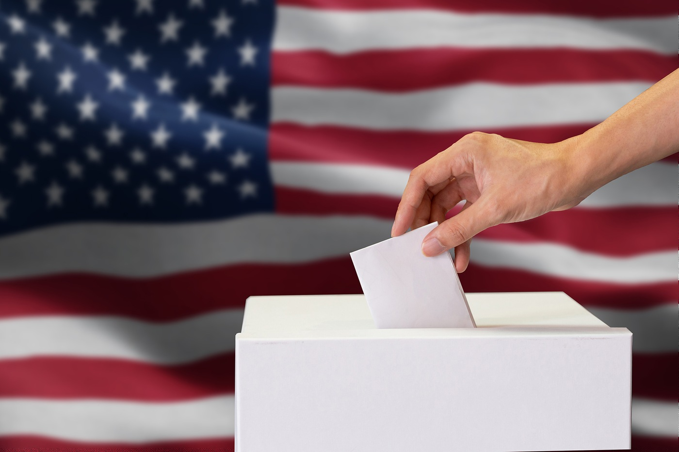 Stock image depicting a person placing a ballot into a ballot box with an American flag background
