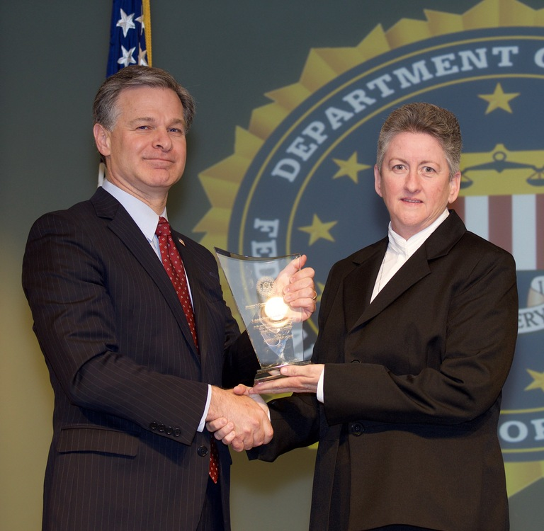 FBI Director Christopher Wray presents Philadelphia Division recipient Guadalupe Family Services (represented by Sister Helen Cole) with the Director's Community Leadership Award (DCLA) at a ceremony at FBI Headquarters on April 20, 2018.