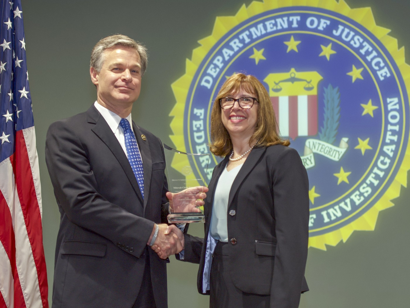 FBI Director Christopher Wray presents Philadelphia Division recipient the Mitzvah Circle Foundation (represented by Fran Held) with the Director's Community Leadership Award (DCLA) at a ceremony at FBI Headquarters on May 3, 2019.