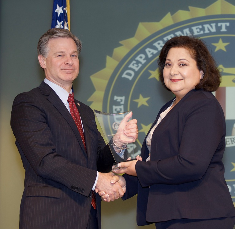 FBI Director Christopher Wray presents Phoenix Division recipient Azra Hussain with the Director's Community Leadership Award (DCLA) at a ceremony at FBI Headquarters on April 20, 2018.