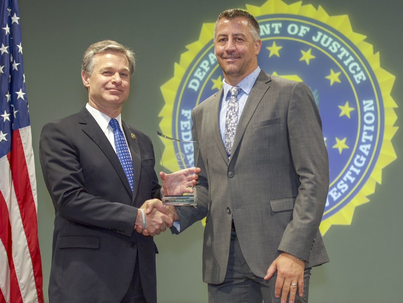 FBI Director Christopher Wray presents Phoenix Division recipient David Gillum with the Director's Community Leadership Award (DCLA) at a ceremony at FBI Headquarters on May 3, 2019.