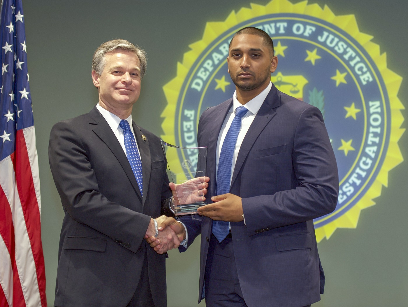 FBI Director Christopher Wray presents Pittsburgh Division recipient Wasiullah Mohamed with the Director's Community Leadership Award (DCLA) at a ceremony at FBI Headquarters on May 3, 2019.