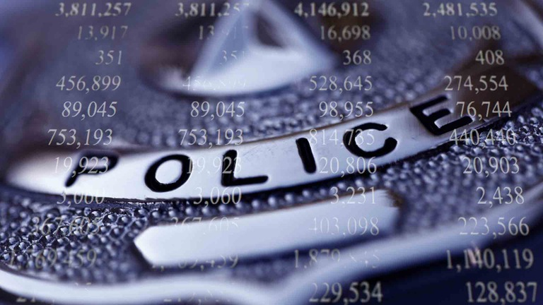 Stock image depicting a police badge with an overlay of numbers representing crime data.