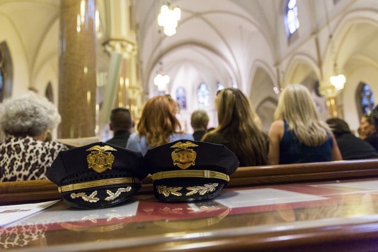 Two police hats sit on a table as attendees listen to the annual National Police Week Blue Mass at St. Patrick's Catholic Church on May 2, 2017 in Washington, D.C.